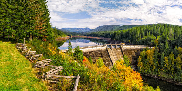 Concrete dam with lake behind it and surrounded by forest with fall colors on the trees