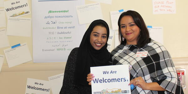 Two women of color holding sign that reads We Are Welcomers.