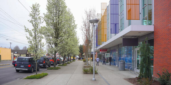 Street view of SE 82nd and Division with colorful multi-use building and pedestrians on sidewalk