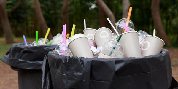 Two garbage cans at a park overflowing with disposable cups, straws and lids.