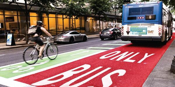 Photo of Bus Only Lane painted red, a TriMet bus, and a bicyclist in the adjacent green bike lane
