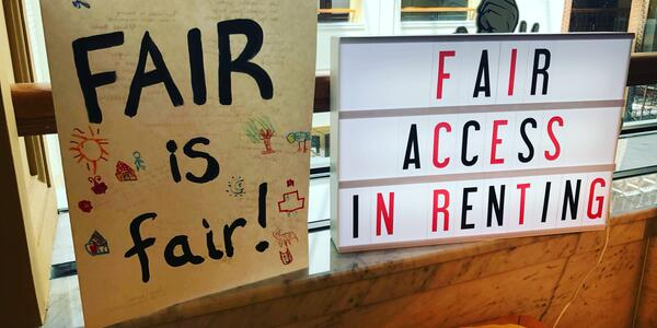 Two signs, one saying FAIR is Fair, one saying Fair Access in Renting