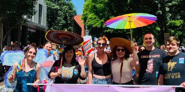 "Commissioner Eudaly and other participants hold a banner entitled ""Support Queer Artists"" and several rainbow parasols at the 2019 Portland Pride Parade"
