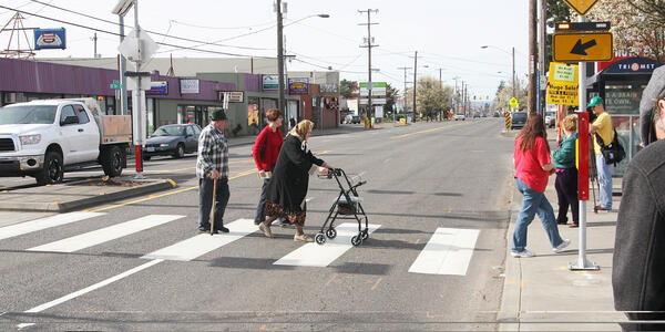 A group of people walk in a crosswalk. One of the people is using a walker and another is using a cane.