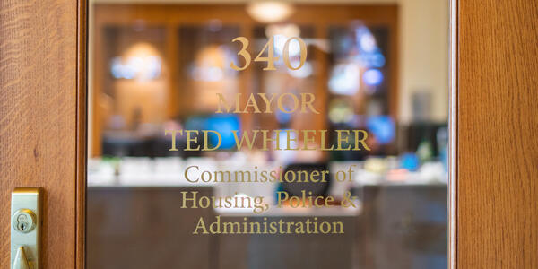 Glass door with a sign that reads 340, Mayor Ted Wheeler, Commissioner of Housing, Police & Administration