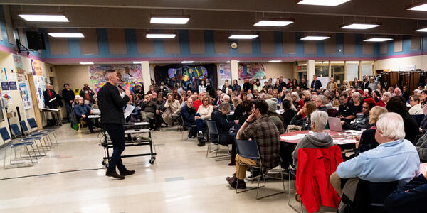 Mayor Wheeler is speaking in front of a large crowd of people seated around multiple tables.