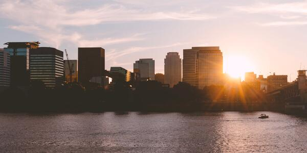 View of Downtown Portland skyline during a bright sunset, viewed from the East side of the Willamette River