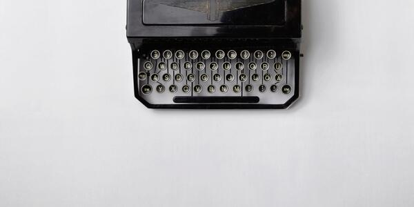 Top down view of a classic black typewriter against a white background.