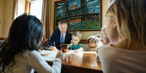 Five children surround Mayor Wheeler while at his desk.