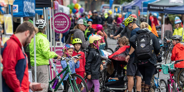 Adults and children with bikes check out vendor booths
