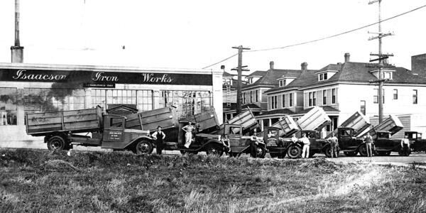 Black and white image of lineup of garbage trucks circa early-1900s