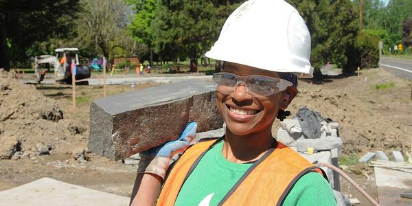 Black woman construction worker holding a large concrete brick