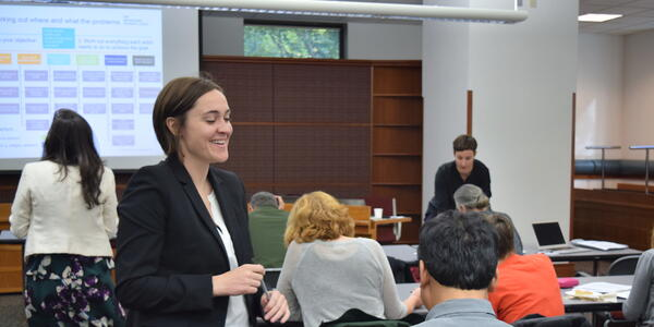 This image from a workshop with the Behavioral Insights Team shows a standing person in a black suit smiling and talking to someone in a grey shirt who is seated at a table. Several other people are seated at other tables in the background, and someone in the background is looking up at a screen on which a process map is projected.