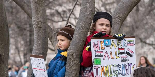"Photo of two children in a tree holding signs saying ""We Are All Immigrants"" and ""Refugees Welcome"" Photo Credit to Equity Corps of Oregon."