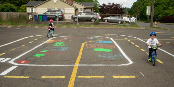 Two children ride bikes at painted traffic playground