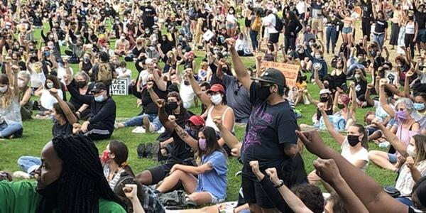 Hundreds of people gather on the grass in Portland Parks & Recreation's Peninsula Park; most wearing face coverings and raising their fists.