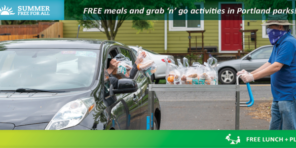 A photo of a community member driving up to a Free Lunch + Play site to pick-up a free lunch.
