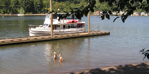Two toddlers wading in Willamette River in front of a docked motorboat