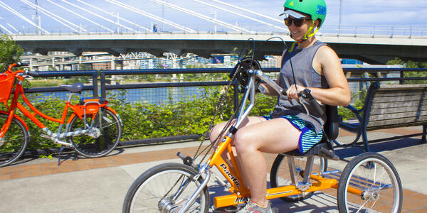Person wearing a helmet riding an adaptive hand-powered tricycle along the Portland waterfront.