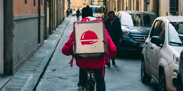 A Photo of a Bicycle Delivery Person Delivering Food in a City Street