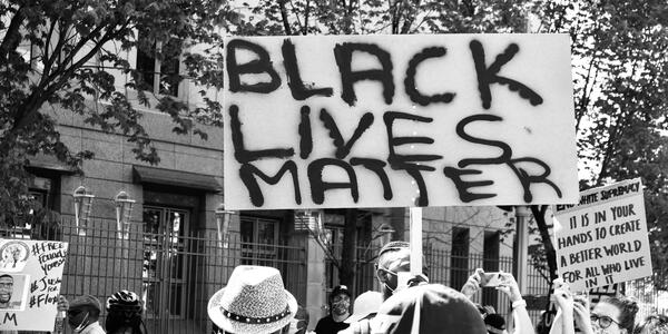 "Black and white image of protesters holding ""Black Lives Matter"" sign and ""It is in your hands to create a better world for all who live in it"" sign"