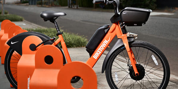 BIKETOWN electric assist bike with orange frame and black basket in front, with BIKETOWN logo with Nike swoosh, docked at a BIKETOWN station along quiet street.