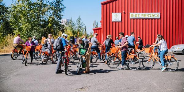 Crowd of folks straddling orange BIKETOWN bike-share rentals, getting ready for a ride.
