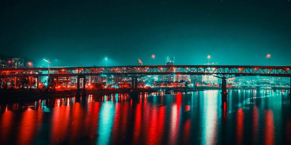 Portland skyline behind bridge at night with bright red and blue lights reflecting off the river.