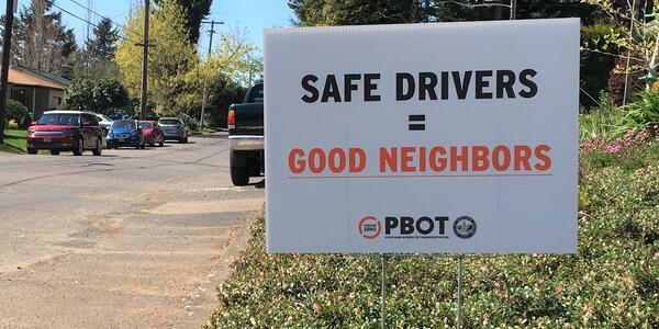 "A lawn sign that reads ""Safe Drivers = Good Neighbors"" in black and orange text on a whitebackground"
