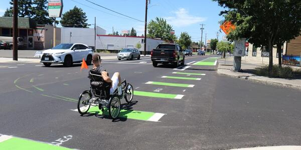 Individual crossing a street using an adaptive bike