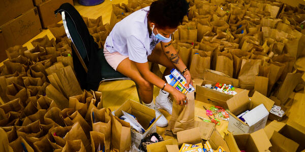 A woman of color sits surrounded by brown paper bags. She is putting in art supplies into these kits to distribute to children.