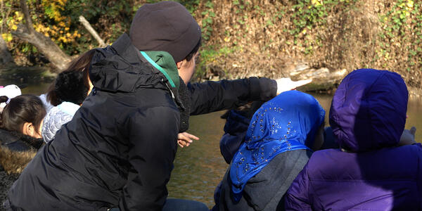 An educator leans down to help students look for birds.