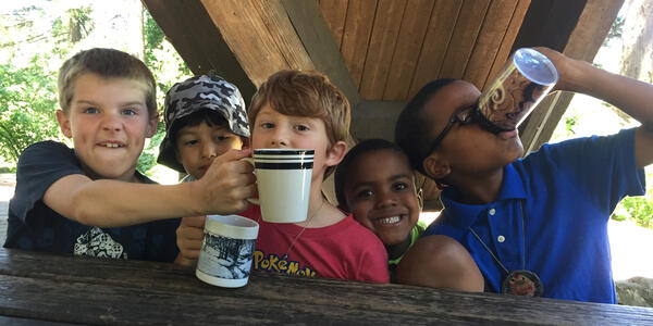 Five boys take a drink of a nature-based tea at Nature Day Camp at Hoyt Arboretum