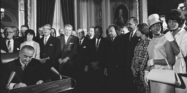 A photo of President Lyndon B. Johnson signing the Voting Rights Act surrounded by lawmakers and Black Americans.