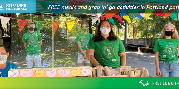 Free Lunch + Play staff members wearing masks and ready to hand out free meals and grab 'n' go activity kits to youth.