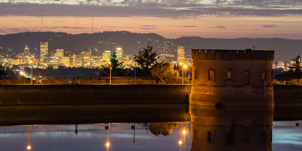Nighttime photo of Mt. Tabor reservoir with the lights of downtown Portland twinkling in the background