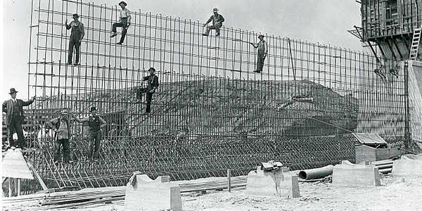 In this historical black and white photo, construction workers climb and pose on the rebar supports at Mount Tabor Reservoir.