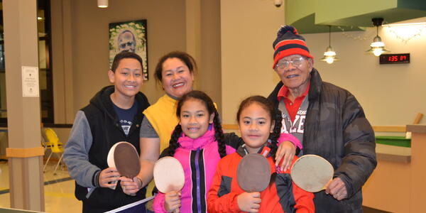 Multigenerational family smiling while holding up table tennis paddles in a Community Center