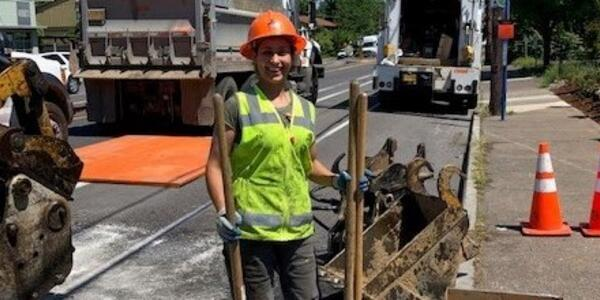 Female construction worker stands by work site on city street.