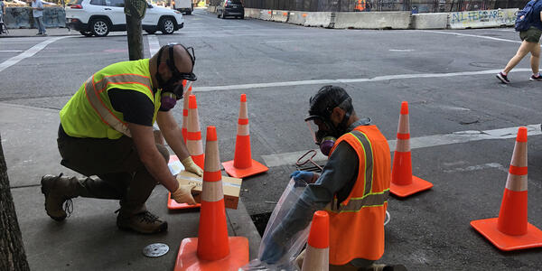 Two workers in reflective collect samples from storm drain from which rack has been removed.