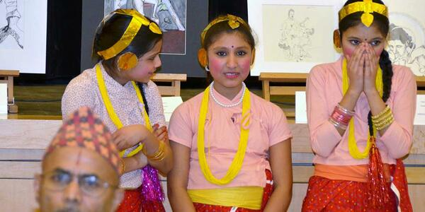 Three young girls stand waiting for a performance.