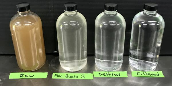 Four bottles of water of differing clarities