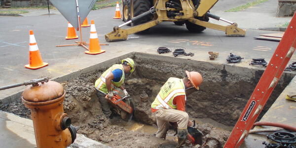 Two workers fix pipes below street level