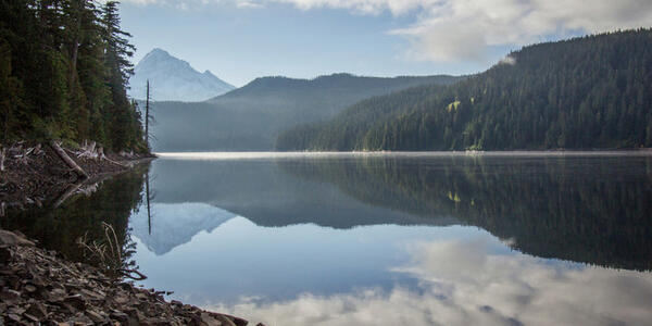 A serene photo of a blue lake reflecting Mt Hood and rolling hills covered in green trees in the background.