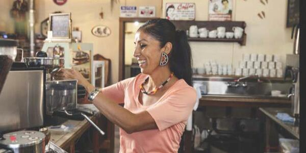 A woman wearing a pink shirt and chunky earrings making coffee