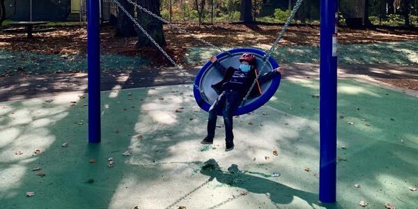 A child on the new accessible swing at Creston Park's playground