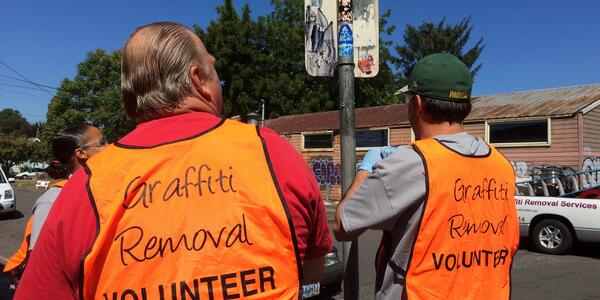"Two volunteers stand with their backs to the camera. They are wearing bright orange vests that say ""Graffiti Removal Volunteer"""
