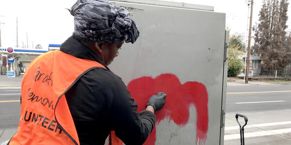 A volunteer works to remove unauthorized graffiti from a utility box.