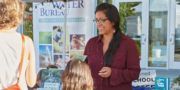 Fabiola Casas tables at water bureau event and talks to woman and young girl