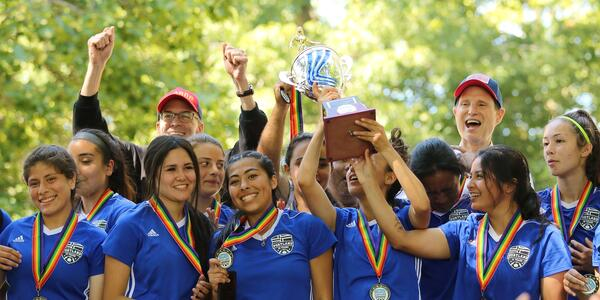 Smiling soccer players raise a trophy while the late former Parks Commissioner Nick Fish cheers